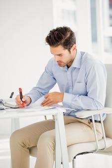 Empresario tomando notas en su escritorio