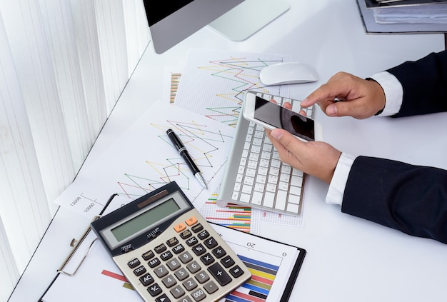 Empresario trabajando con modernos dispositivos, computadora y teléfono móvil.