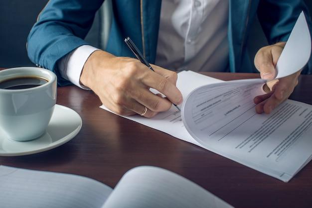 Empresario en traje firmando documentos