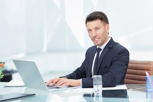 Empresario en traje negro sentado detrás de un escritorio