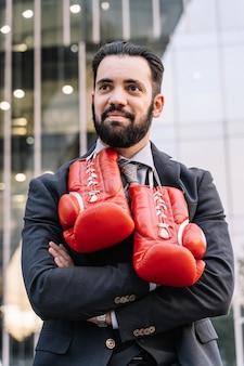 Empresario en un traje, reloj y guantes de boxeo colgando de su cuello con las manos cruzadas frente a algunos edificios