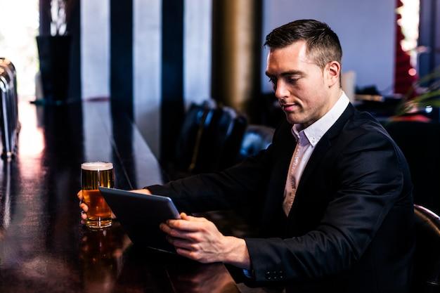 Empresario usando tableta con una cerveza en un bar