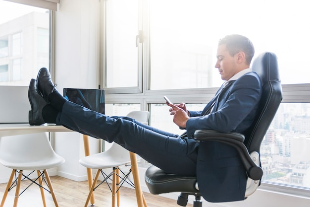 Empresario usando un teléfono celular sentado en un sillón con su pierna cruzada sobre la mesa