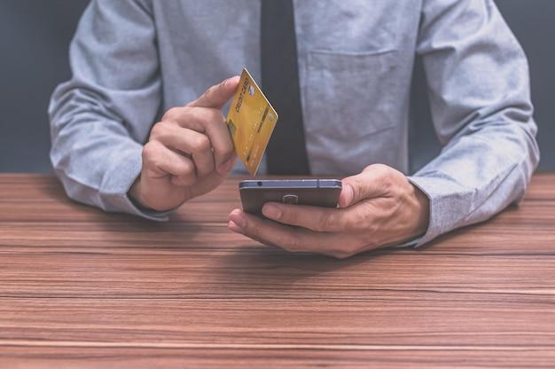 El empresario utiliza la tarjeta de crédito para comprar en línea a través de teléfonos inteligentes.