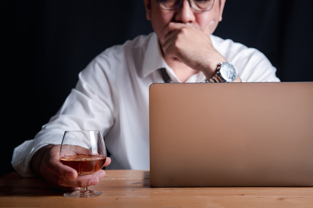 Un empresario con un vaso de whisky por el estrés de trabajar duro por la noche