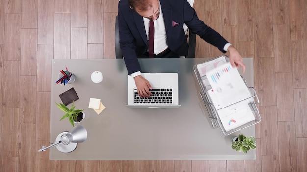 Empresario de vista superior escribiendo y leyendo datos de un gráfico