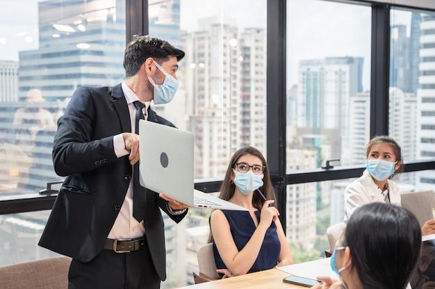 Empresario vistiendo mascarilla con presentación del plan de negocios en portátil