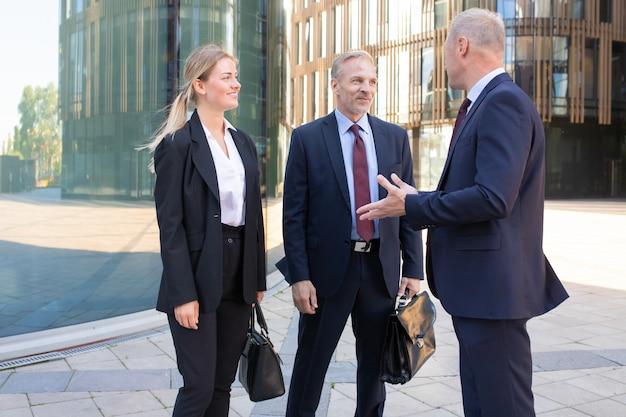 Empresarios adultos profesionales confiados que se encuentran al aire libre. contenido hombre y mujer de negocios en traje escuchando jefe y sonriendo. concepto de trabajo en equipo, negociación y asociación