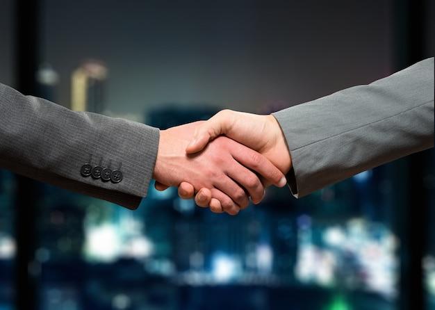 Empresarios agitando sus manos en la noche