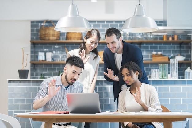 Empresarios agitando sus manos hacia la pantalla del pc