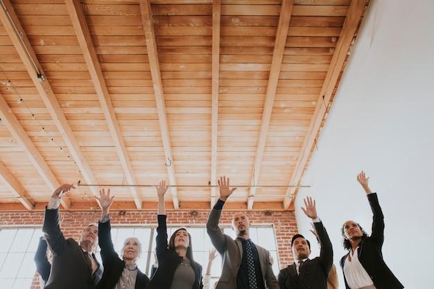 Empresarios alegres levantando las manos en el aire