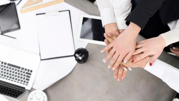 Empresarios apilando la mano del otro sobre el escritorio