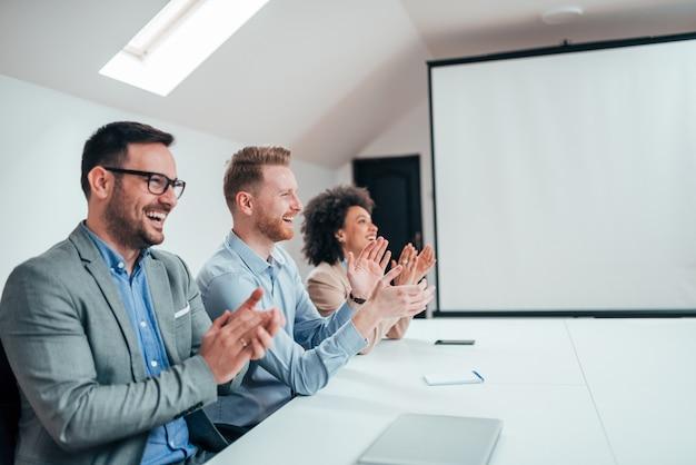 Empresarios aplauden en una reunión en una oficina moderna.