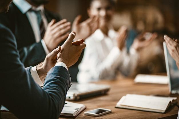Empresarios aplauden durante la reunión en la sala de juntas
