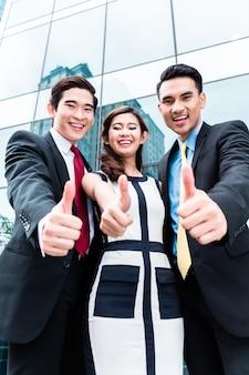 Empresarios asiáticos afuera frente a rascacielos