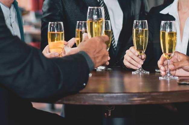 Los empresarios asiáticos bebiendo celebran el éxito empresarial feliz