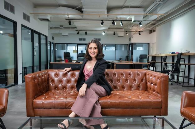 Empresarios asiáticos confía en sentarse y sonreír en el sofá vintage en el espacio de coworking