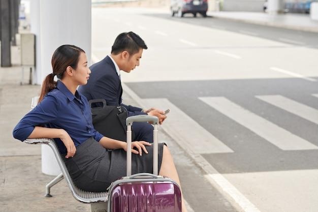 Empresarios asiáticos esperando taxi en el aeropuerto