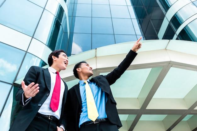 Empresarios asiáticos frente a edificio de gran altura