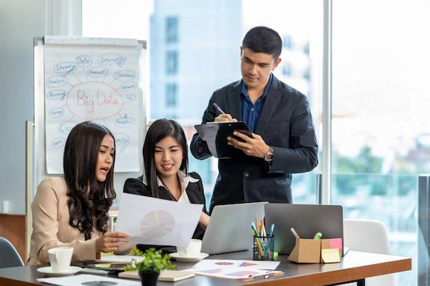 Empresarios asiáticos y multiétnicos con trajes formales trabajando y compartiendo ideas
