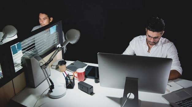 Empresarios asiáticos que se alojan en horas extras por la noche trabajando en la oficina