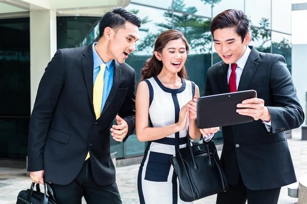 Empresarios asiáticos trabajando afuera en tablet pc