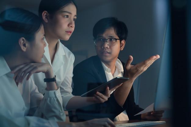 Empresarios asiáticos trabajando duro tarde juntos y planeando con la computadora en la oficina por la noche