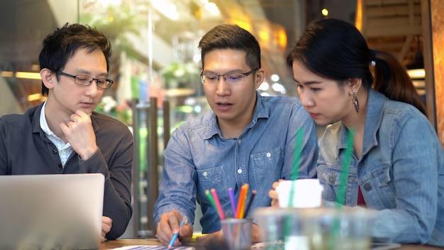 Empresarios asiáticos con traje casual trabajando y compartiendo ideas