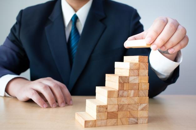 Empresarios de bloques de madera de mano apilados juntos para desarrollar un escalón