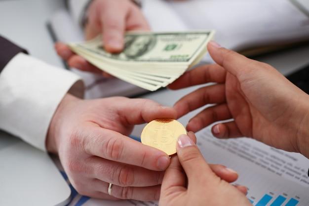 Los empresarios cambian de moneda hacen un trato exitoso mantienen el dinero en armas