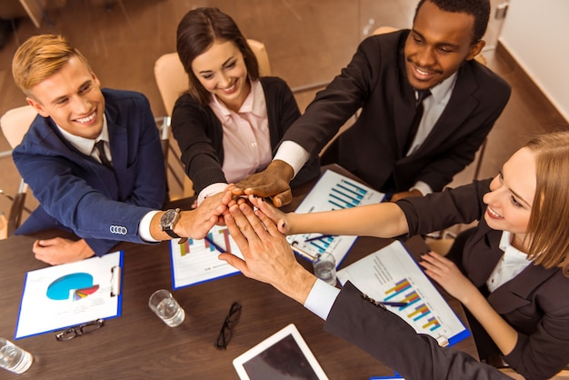 Empresarios cogidos de la mano en equipo.