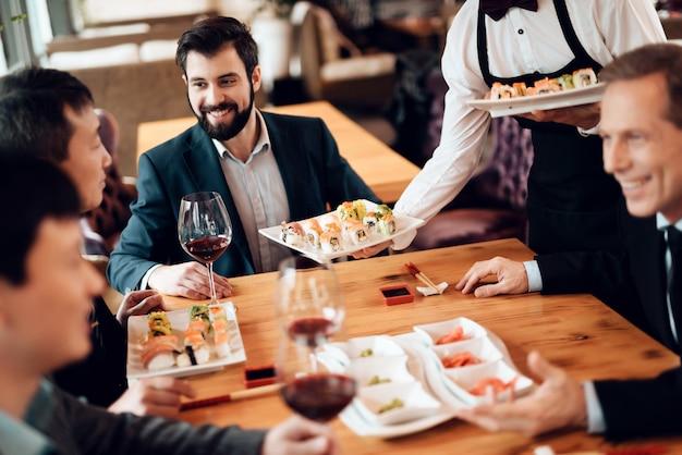 Los empresarios comen juntos en un restaurante.