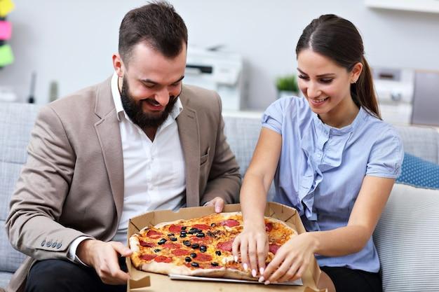 Empresarios comiendo pizza en la oficina