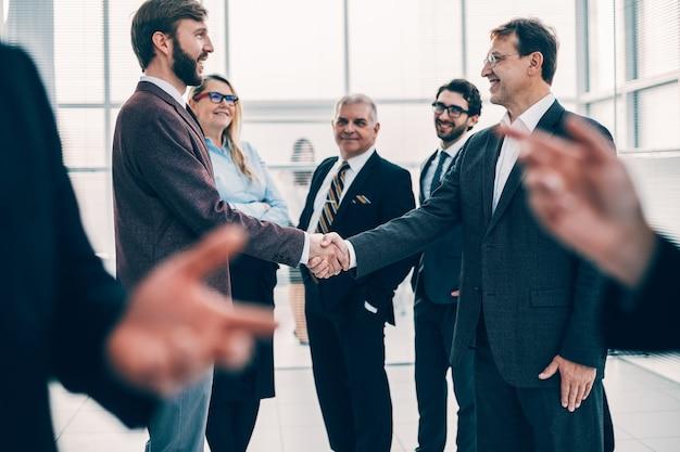 Empresarios confiados dándose la mano unos a otros