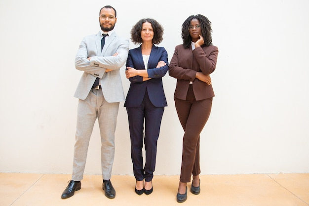 Empresarios confiados posando con los brazos cruzados