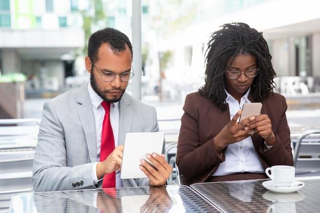 Empresarios confiados que usan dispositivos modernos