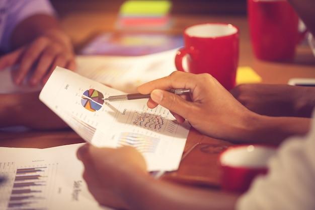 Los empresarios consultan a la reunión financiera del asesor para analizar y sobre el informe financiero en la sala de su oficina