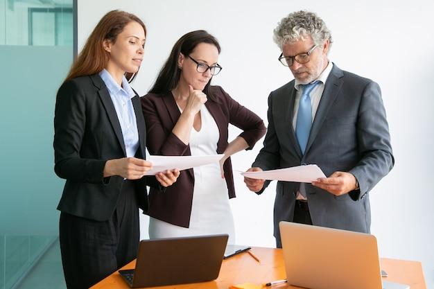 Empresarios de contenido discutiendo el proyecto, viendo documentos y parados juntos cerca de la mesa con computadoras portátiles