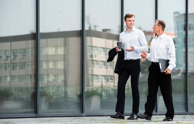 Empresarios conversando mientras caminan