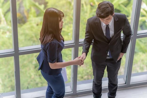 Empresarios se dan la mano con una mujer en la oficina