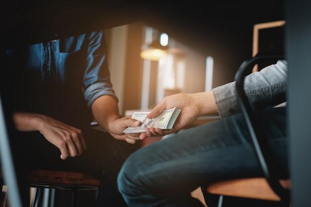 Empresarios dando soborno dinero debajo de la mesa