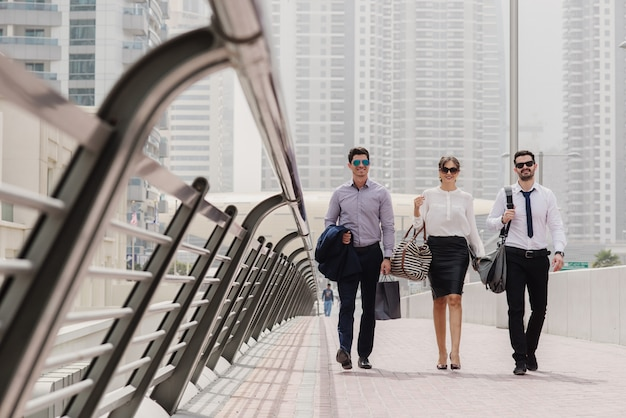 Empresarios en dubai marine caminando hacia su oficina y hablando sobre nuevos movimientos de marketing e ideas.