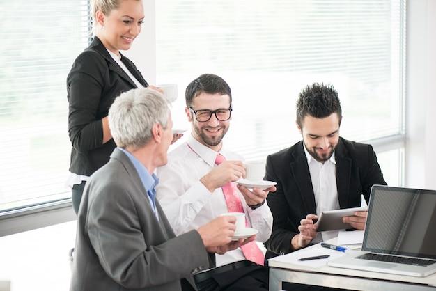 Empresarios y ejecutivos reunidos usando laptop
