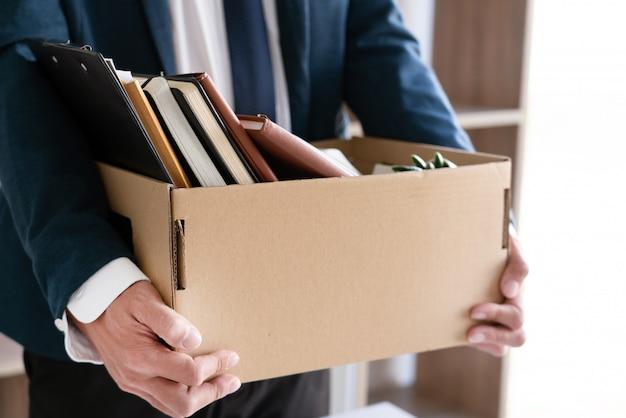 Los empresarios de empleados jóvenes despedidos tristes tienen cajas que incluyen plantas de maceta y documentos para el desempleo de sus pertenencias personales, concepto resignado.
