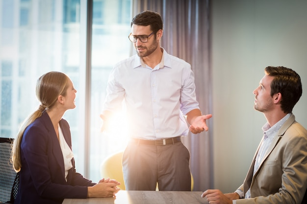 Empresarios y empresaria interactuando en su escritorio