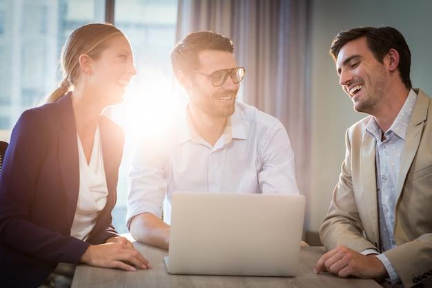 Empresarios y empresaria interactuando usando laptop