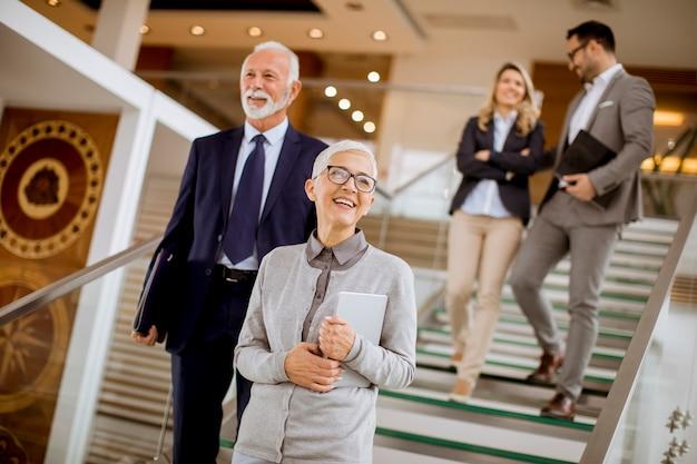Empresarios y empresarias caminando y subiendo escaleras en un edificio de oficinas