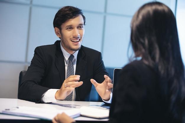 Empresarios y empresarias discutiendo documentos por concepto de entrevista de trabajo