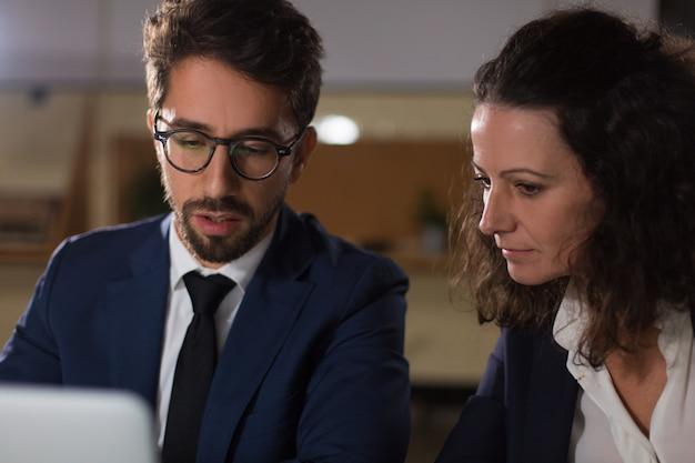 Empresarios enfocados trabajando con laptop