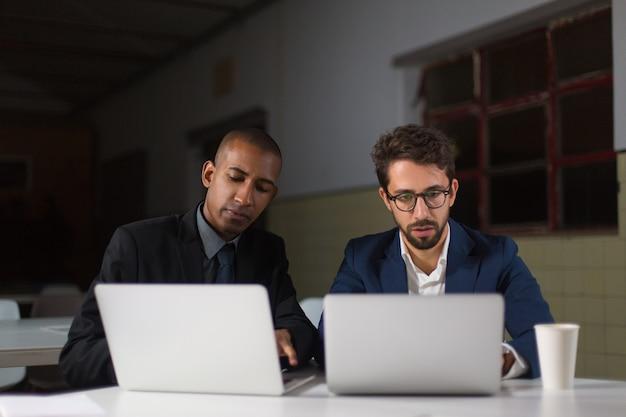 Empresarios enfocados usando computadoras portátiles